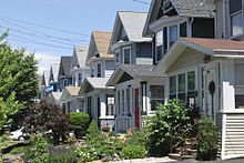 Two-story, single-family homes line a street; the houses are identical in design except for color.