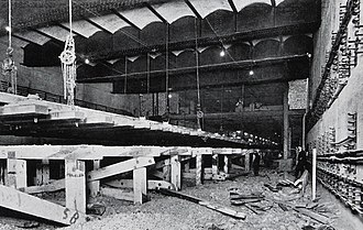 Aldgate East tube station - The reconstruction of Aldgate East station in progress. To lower the track level, the trackbed has been excavated with an interim support of timber trestles. Then, with the tracks attached to chains from the ceiling, the trestle was dismantled and the tracks lowered down to the new lower track level.