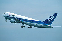 An All Nippon Airways in blue and white livery during takeoff, with landing gears still down.