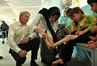Andrew Mitchell looks on as a child receives treatment in Kabul (6302119536).jpg