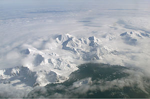 Aerial view of a range of icy mountains with a coastline visible in the foreground