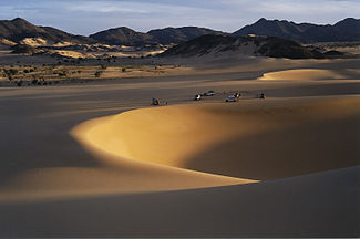 Sand dunes in the desert, offroad vehicles and mountains in the distance.