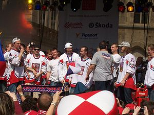 Ice hockey players wearing red and white uniforms stand elevated on a stage facing out towards a crowd of people.