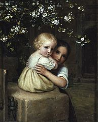 Girl holding a child under a blossoming apple tree