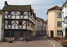 Street scene. On the left of the road is a half timbered house where the first and second storeys have irregular black wooden beams showing through white painted walls.