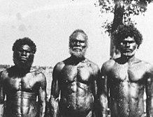 drei Aborigines verschiedenen Alters mit muskulösen Oberkörpern welche mit ernstem Blick in die Kamera schauen