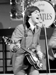 Paul McCartney en concert avec les Beatles, guitare basse en main, livrant une performance énergique