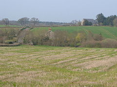 A few buildings scattered among fields and trees.