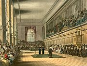 This early 19th-century picture shows the Great Hall on St. Matthew's Day, 21 September. On this day, two Grecians destined for scholarships to Oxford and Cambridge Universities gave orations in praise of the school, one in Latin and the other in English. The Verrio painting can be seen along the wall on the right.