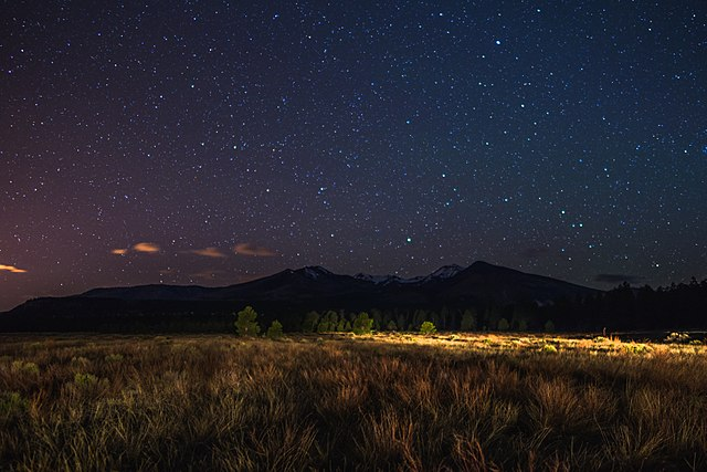 A field and mountain at night. The field shows no damage from the fire which destroyed it seven years earlier