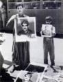 Boys selling posters of Abd al-Karim Qasim, Baghdad, 1959.png