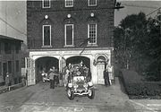 1930s fire engines leaving a brick firehouse