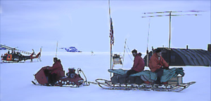 Sleds pulled by snowmobiles or dogs provided transportation between camps McMurdo Station right background (around 1960).