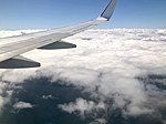 Cabin window view of clouds & aircraft wing over Queensland.jpg