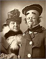 Head and shoulder shot of two men looking at the camera in pantomime costumes