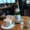 Cappuccino coffee and Aqua Panna mineral water on table.jpg