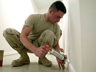 Caulk - Man applying caulk to baseboard