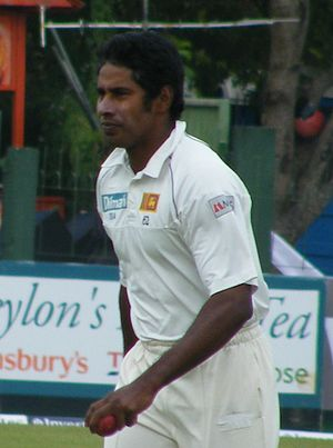 Vaas, dressed in cricket whites and holding cricket ball in left hand, preparing to start his bowling run up.