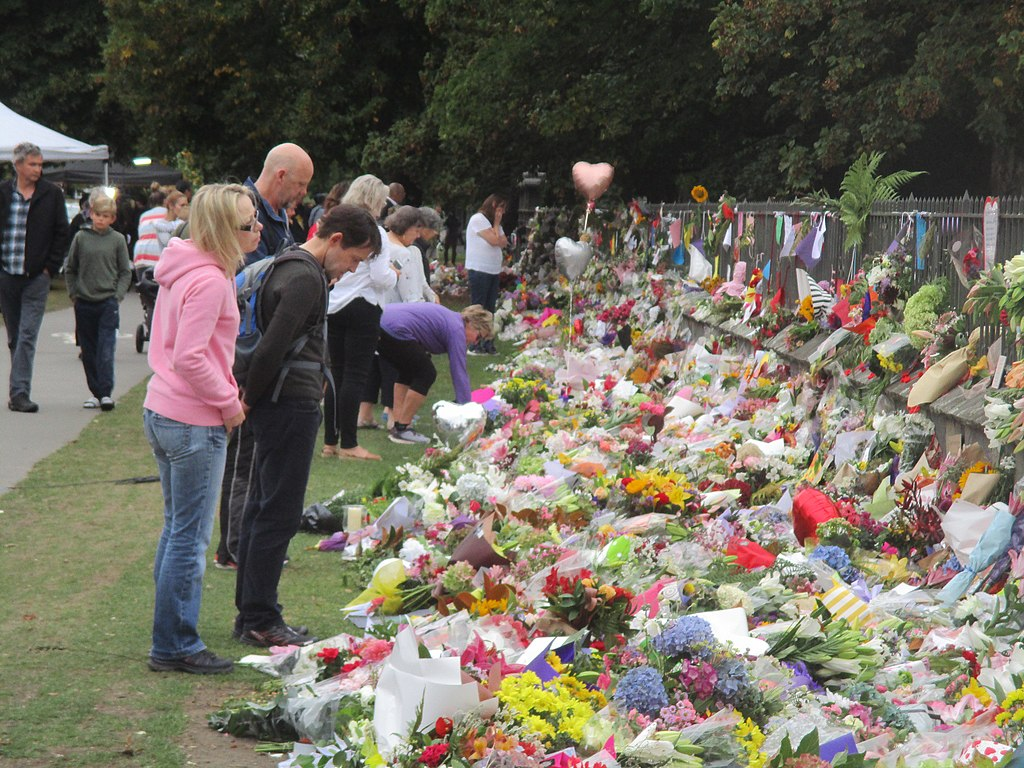 A group of people look at a large, colourful array of flowers and foil balloons set against a wooden fence.