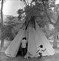 Clifford Jake demonstrates setting up a tipi while girl runs past him at the first annual Folklife Festival, Zion National Park (4a96612a7d50485fac84d80f88b11378).jpg