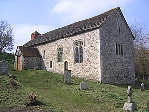 Three-quarter view of a long, low, flint rubble church on a rising grass slope with some gravestones.  A tile-roofed porch juts out from the longer side, which also has two paired lancet windows and two other windows.  The shorter side has three single-light round-headed windows and a blocked lancet window below the roofline.