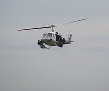 A helicopter flying with four special police troops standing on its landing skids
