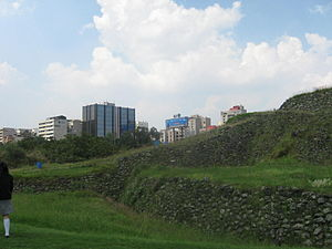 Cuicuilco - Stairway portion of the Cuicuilco pyramid with modern buildings of the Coyoacán borough in the background