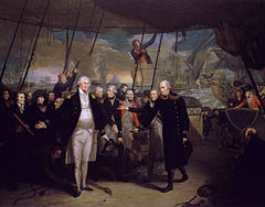 On the deck of a sailing warship, with men in blue and red military uniforms standing in a line, a man in a long blue coat passes a sword to a large man in a short, open blue coat, who holds his hands wide with their palms flat. In the background several ships in various states of disrepair drift between columns of smoke with the sun low on the horizon.