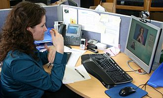 Video relay service - Image: Deaf or Ho H person at her workplace using a Video Relay Service to communicate with a hearing person via a video interpreter and sign language IMG 2954