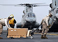 Defense.gov News Photo 110321-N-SO729-408 - U.S. Marines move humanitarian and disaster relief supplies to load them into a Marine Corps CH-46E Sea Knight helicopter on the flight deck of the.jpg