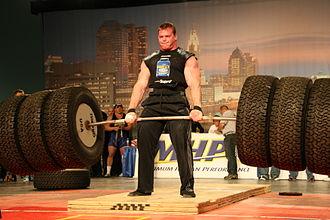 Deadlift - A man deadlifts using tires as weights.