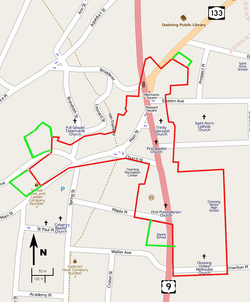 A map of the streets in downtown Ossining, on a gray background with major roads in pink and orange and the locations of some landmarks indicated. The border of the irregularly-shaped historic district is in red. Four small green-bordered areas are adjacent to it.