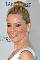 Elizabeth Banks, a blonde-haired caucasian woman in her early 40s, wears a white dress. She wears her blonde hair up in a ponytail.