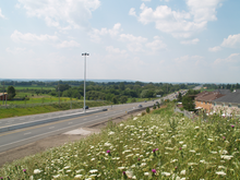 A freeway changes into a four lanes conventional road, and vanishes into the rural foothills