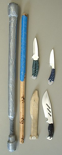 A collection of training weapons used in an Eskrima class.  Includes a padded stick, a rattan stick, a wooden training knife, and a collection of aluminum training knives.