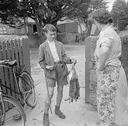 Photo en noir et blanc d'un jeune garçon avec un fusil rapportant deux lapins morts à sa mère