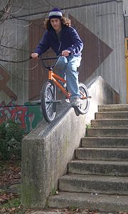 mit dem Vorderrad und dem hinteren Peg auf der Mauer grindet (rutscht) ein BMX-Fahrer den so genannten Feeble-Grind
