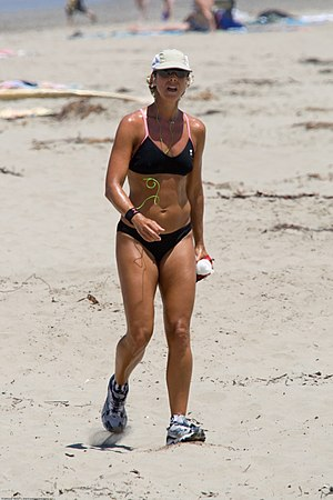 Physical fitness - A female jogging at a beach in U.S. for maintaining/improving her physical fitness.