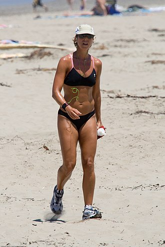 Physical fitness - A woman jogging at a beach in the U.S. to maintain/improve her physical fitness