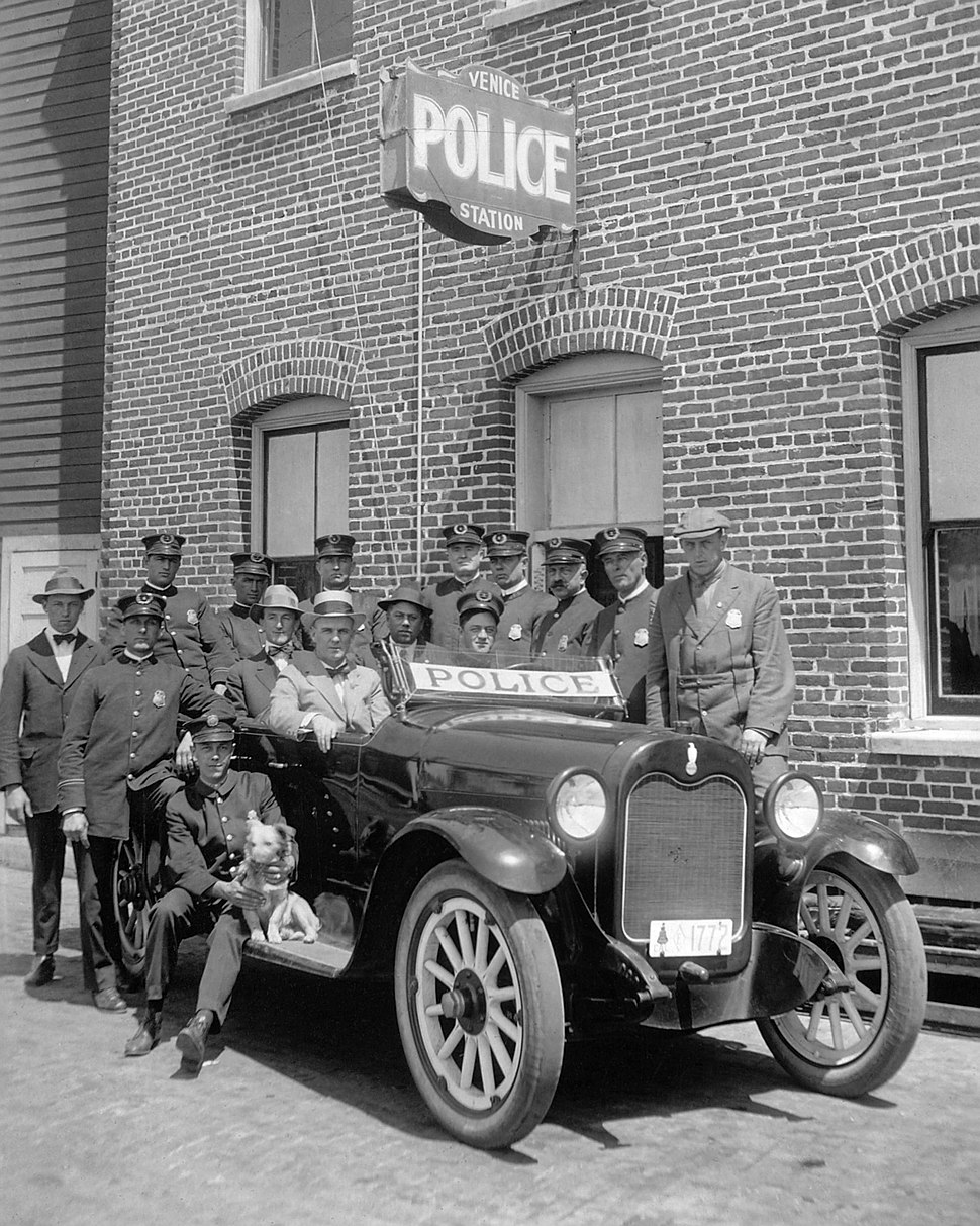 Fifteen uniformed policemen gather around a police car adjacent to the Venice Police Station, ca.1920