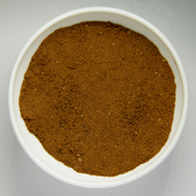 Finely grounded coffee beans in white bowl.png