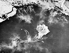 Black and white photograph of a warship moored near a snowy shore viewed from the air. Smoke is issuing from the warship.