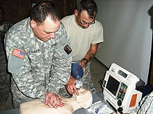 Two men perform CPR on a CPR doll