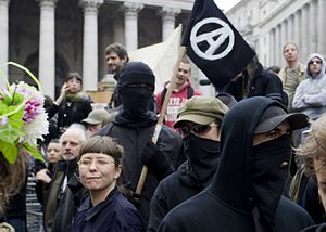 Masked and black clad Anarchist protesters at ...