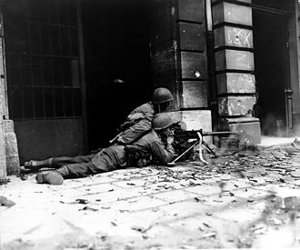 Battle of Aachen - GI M1919 machine gun crew in action against German defenders in the streets of Aachen on 15 October 1944