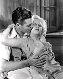 A young, platinum blonde woman in a satin dress is draped across a seated young, dark haired man with her arms raised up behind her, reaching behind his neck while his hands are resting on her torso, and he nuzzles her cheek.