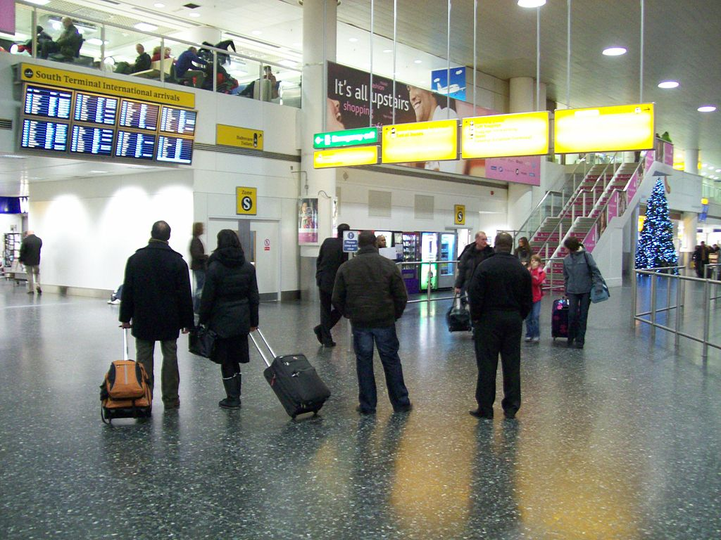 Passengers with luggage looking at arriving-flights board