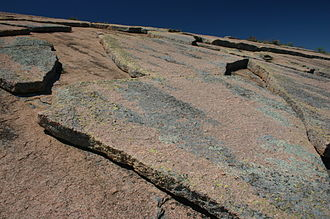 Weathering - Pressure release could have caused the exfoliated granite sheets shown in the picture.