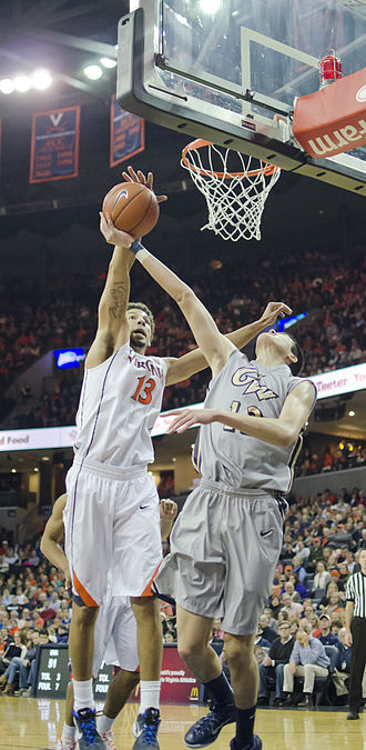 John Paul Jones Arena - Anthony Gill blocking a shot in 2014, with JPJ interior as backdrop