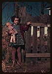 Girl with doll standing by fence1a34429v.jpg